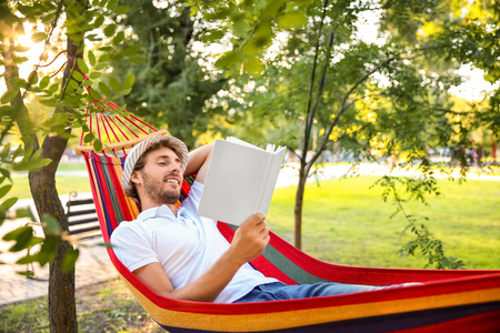 Handsome young man with book resting in hammock outdoors Imagens - 115229449
