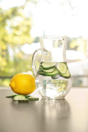 Jug of fresh cucumber water on grey table