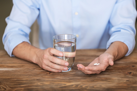 Man holding pills and glass of water at wooden table, closeup