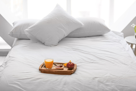 Wooden tray with delicious breakfast on bed Stockfoto