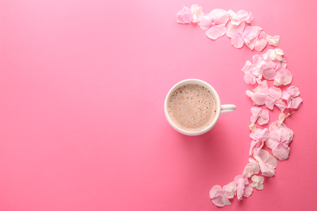 Beautiful flowers and cup of coffee on pink background