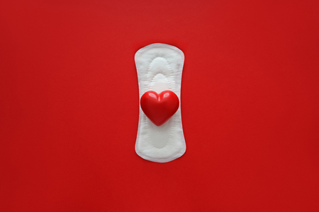 Menstrual pad with red heart on color background Фото со стока