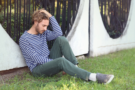 Stressed young man near fence outdoors