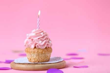 Delicious birthday cupcake with burning candle on color background Standard-Bild - 115238753