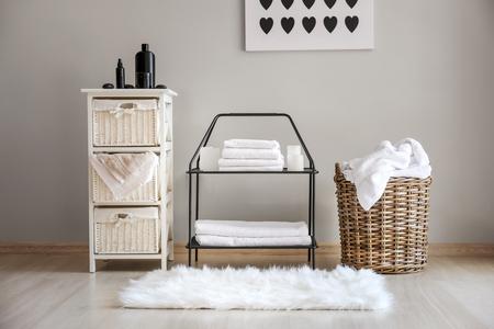 Weidenkörbe mit schmutziger Wäsche und gefalteten sauberen Handtüchern auf Regalen
