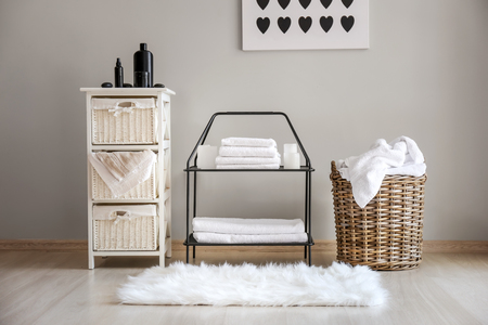 Wicker baskets with dirty laundry and folded clean towels on shelves Standard-Bild - 115238828