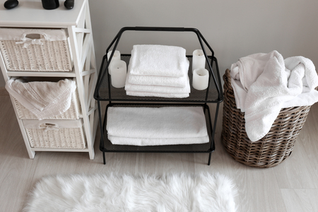 Wicker baskets with dirty laundry and folded clean towels on shelves