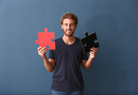 Young man with pieces of jigsaw puzzle on color background