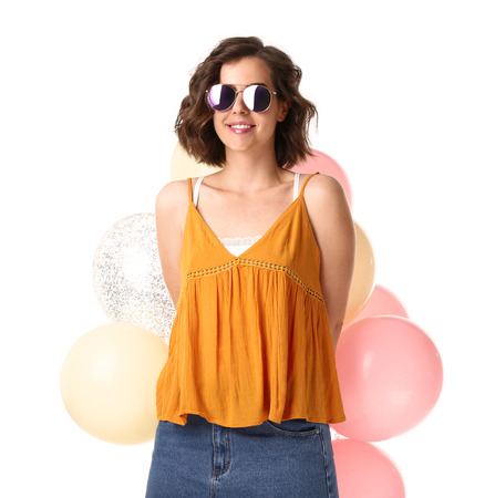 Beautiful young woman with air balloons on white background