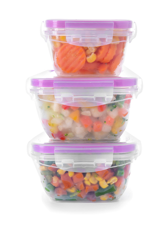 Plastic containers with frozen vegetables on white background