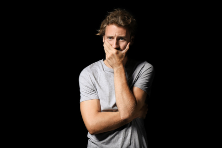 Stressed young man on dark background Stock Photo