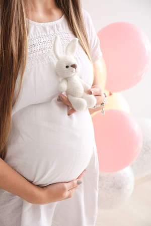 Beautiful pregnant woman with toy on white background