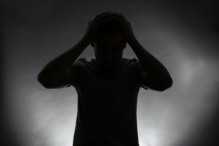 Silhouette of stressed man on dark background Stock Photo
