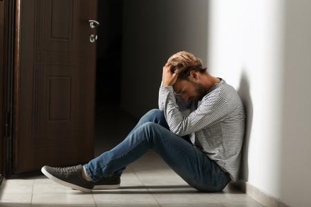 Depressed young man sitting on floor in dark corridor Stockfoto