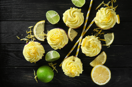 Delicious lemon cupcakes on wooden table, top view