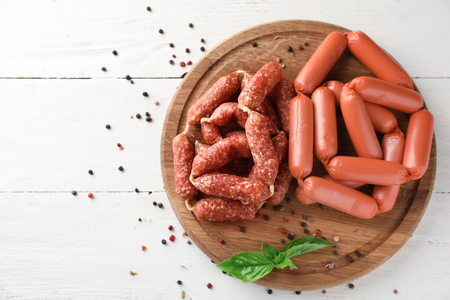 Wooden board with delicious sausages on white table