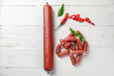 Delicious smoked sausages with chili pepper and basil on white wooden table
