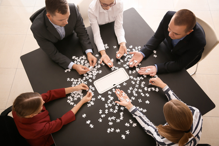 Business team assembling puzzle on dark table