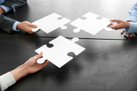 Business team with pieces of puzzle on dark table