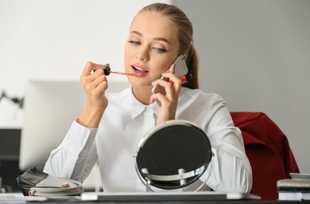 Beautiful female secretary applying makeup while talking on mobile phone in office Stock Photo
