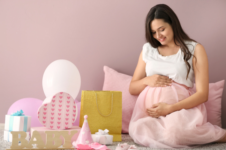 Beautiful pregnant woman with baby shower gifts at home