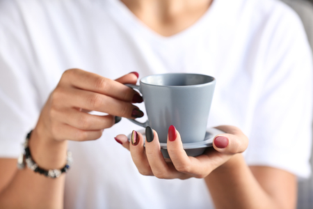 Woman with stylish beautiful manicure drinking coffee, closeup