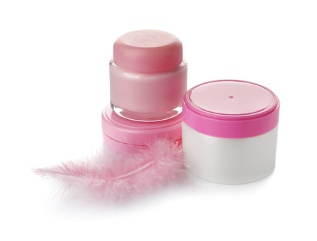 Jars with body cream and pink feather on white background