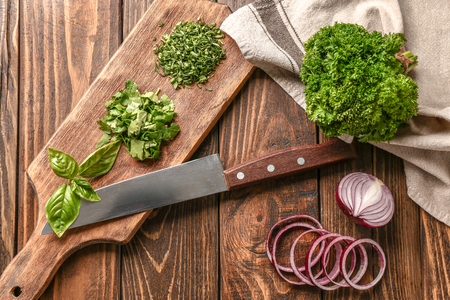 Fresh aromatic herbs with onion and cutting board on wooden background Imagens