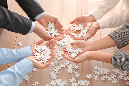 Business team holding pieces of puzzle over wooden table, closeup