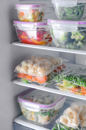 Containers and plastic bags with frozen vegetables in refrigerator Фото со стока