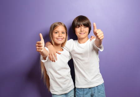 Hugging boy and girl in t-shirts showing thumb-up on color background Archivio Fotografico