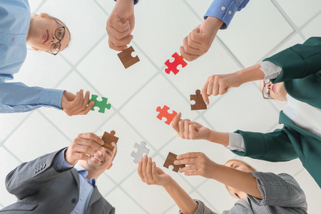 Business team with pieces of puzzle in office, bottom view
