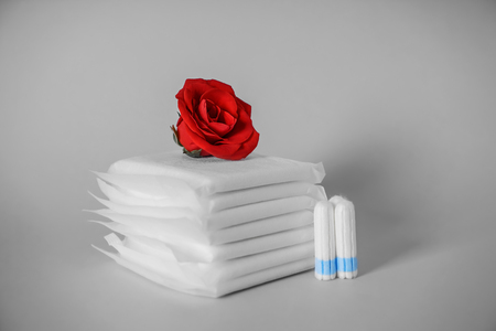 Stack of menstrual pads with red rose and tampons on grey background Stock Photo