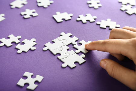 Hand of woman doing puzzle on color background, closeup
