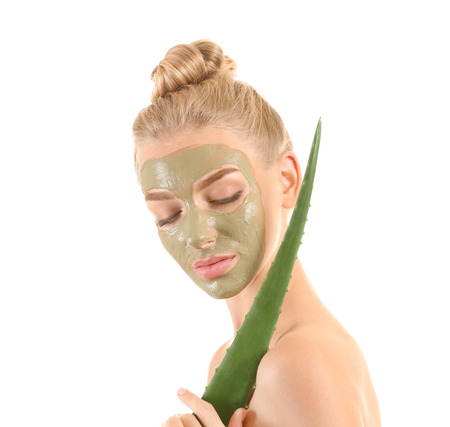 Beautiful young woman with facial mask containing aloe vera extract, on white background