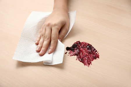 Woman wiping spot of jam on wooden table with paper towel Reklamní fotografie