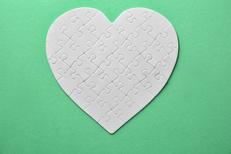 Heart-shaped jigsaw puzzle on color background
