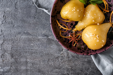Plate with delicious poached pears in wine on grey table