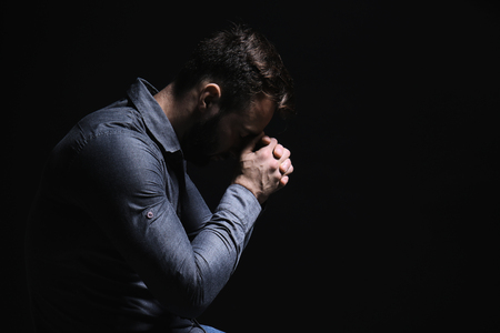 Religious young man praying to God on black background Foto de archivo