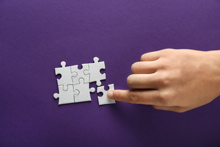 Hand of woman doing puzzle on color background Banque d'images