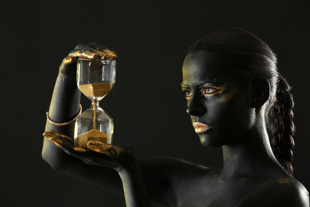 Beautiful woman with black and golden paint on her body holding hourglass against dark background 免版税图像