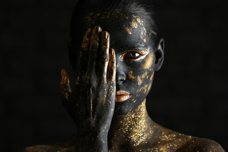 Beautiful woman with black and golden paint on her body against dark background Stockfoto