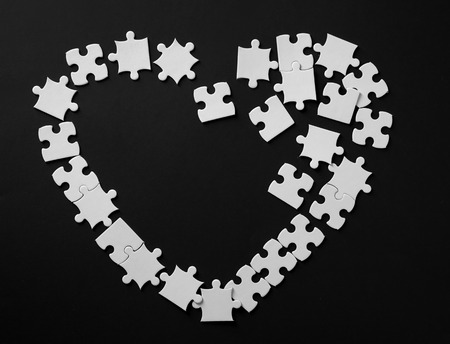 Heart made of jigsaw puzzle pieces on dark background