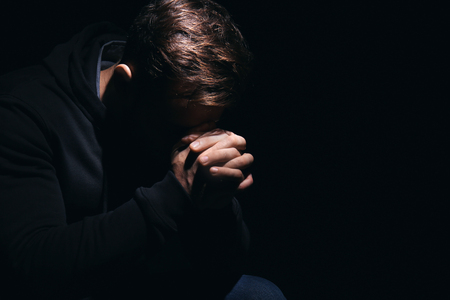 Religious young man praying to God on black background Archivio Fotografico