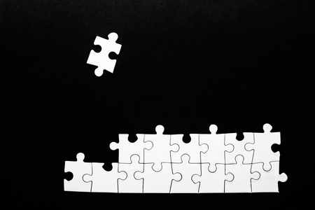 Incomplete jigsaw puzzle on dark background
