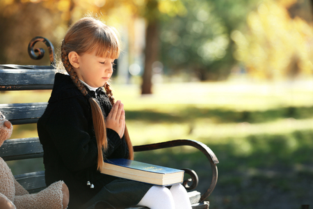 Little girl with Bible praying on bench outdoors Stock Photo