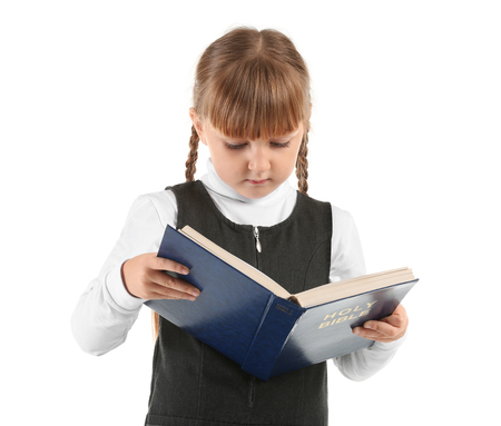 Little girl reading Bible on white background Foto de archivo