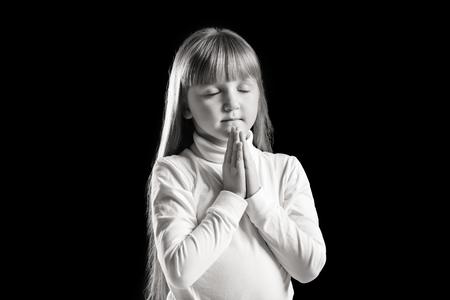 Little girl praying on dark background, black and white effect Stock Photo