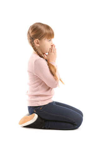 Little girl praying on white background
