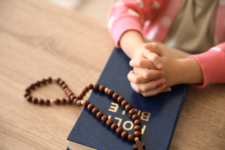 Little girl with Bible praying at wooden table Stock Photo